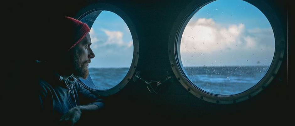 Man on boat looking out of windows - Photo:Innovation Norway
