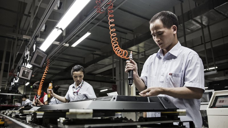 Workers assemble monitors at a factory in Huizhou, Guangdong province
