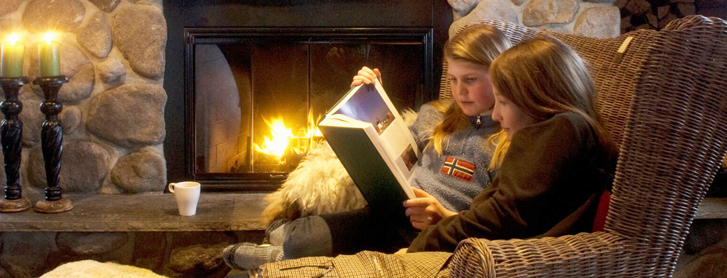 Two girls reaading a book in front of the fire place - Photo:Photo: CH/Innovation Norway